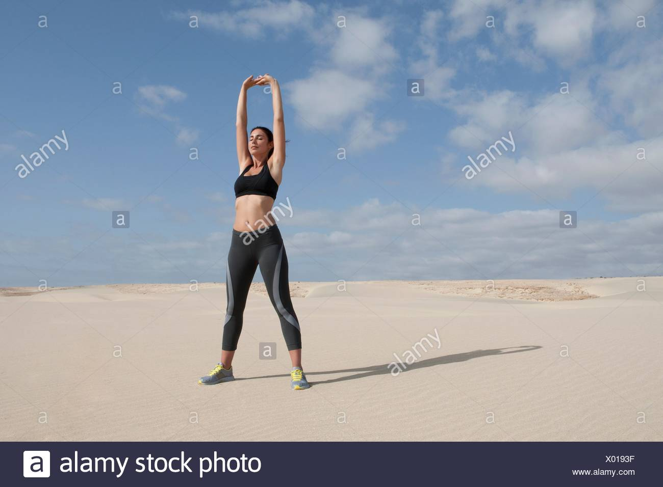 Mujer adulta media el ejercicio con los brazos levantados en la playa Imagen De Stock
