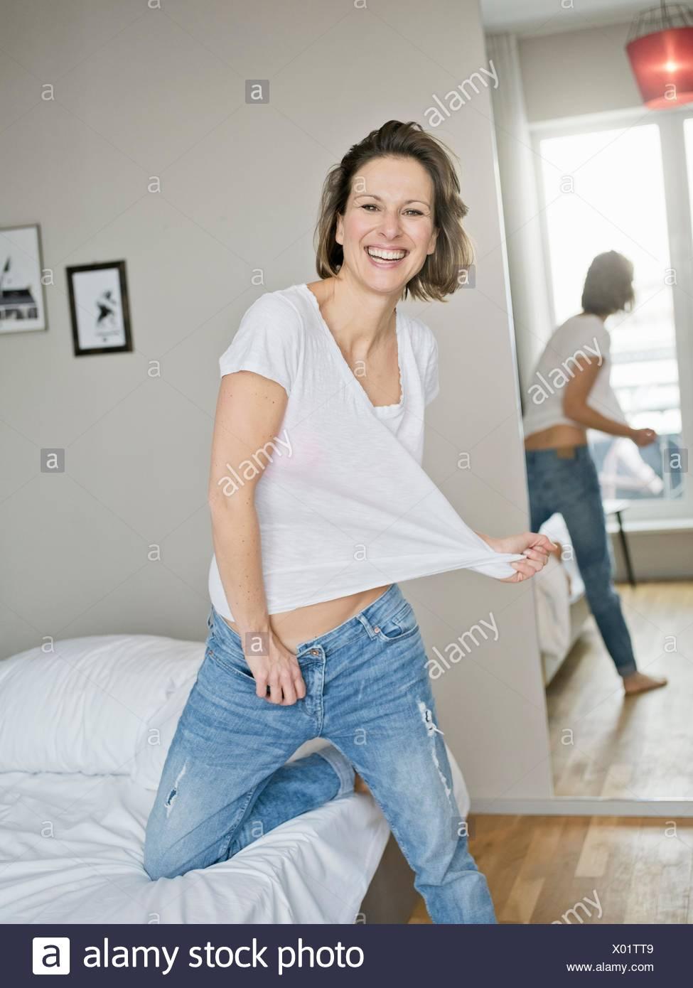 Retrato de mujer madura de rodillas en la cama tirando tshirt Imagen De Stock