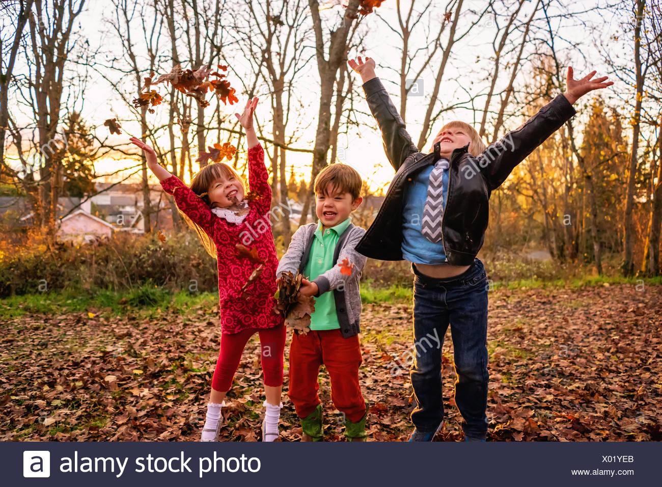 Dos niños y una niña arrojando deja en el aire Foto de stock