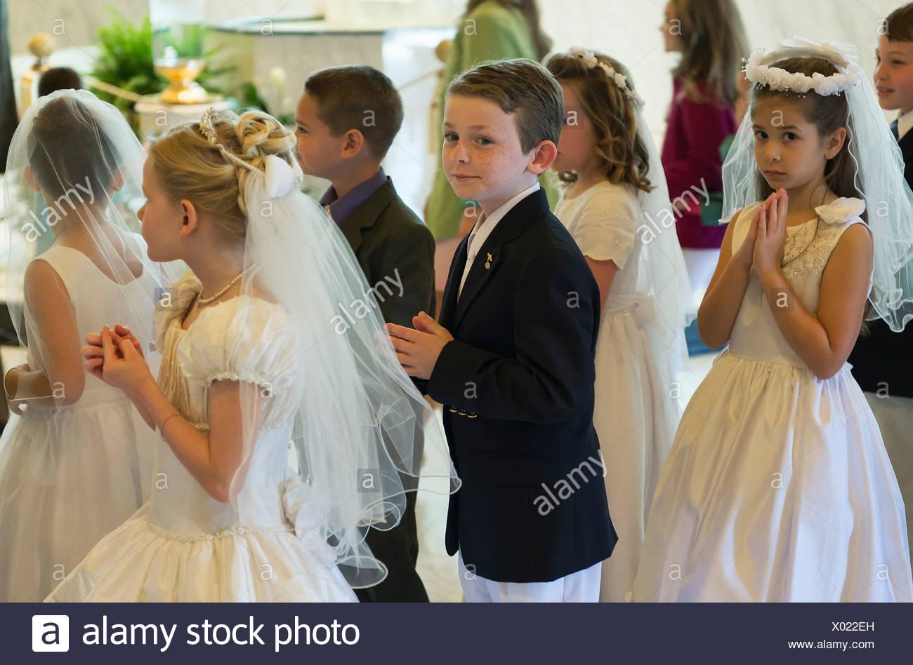 Los niños y niñas católicos reciben el sacramento de la primera comunión. Imagen De Stock
