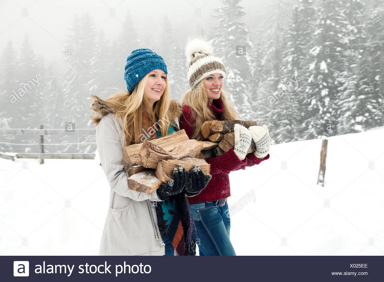 Dos amigas jóvenes que transportaban troncos con nieve mist Imagen De Stock