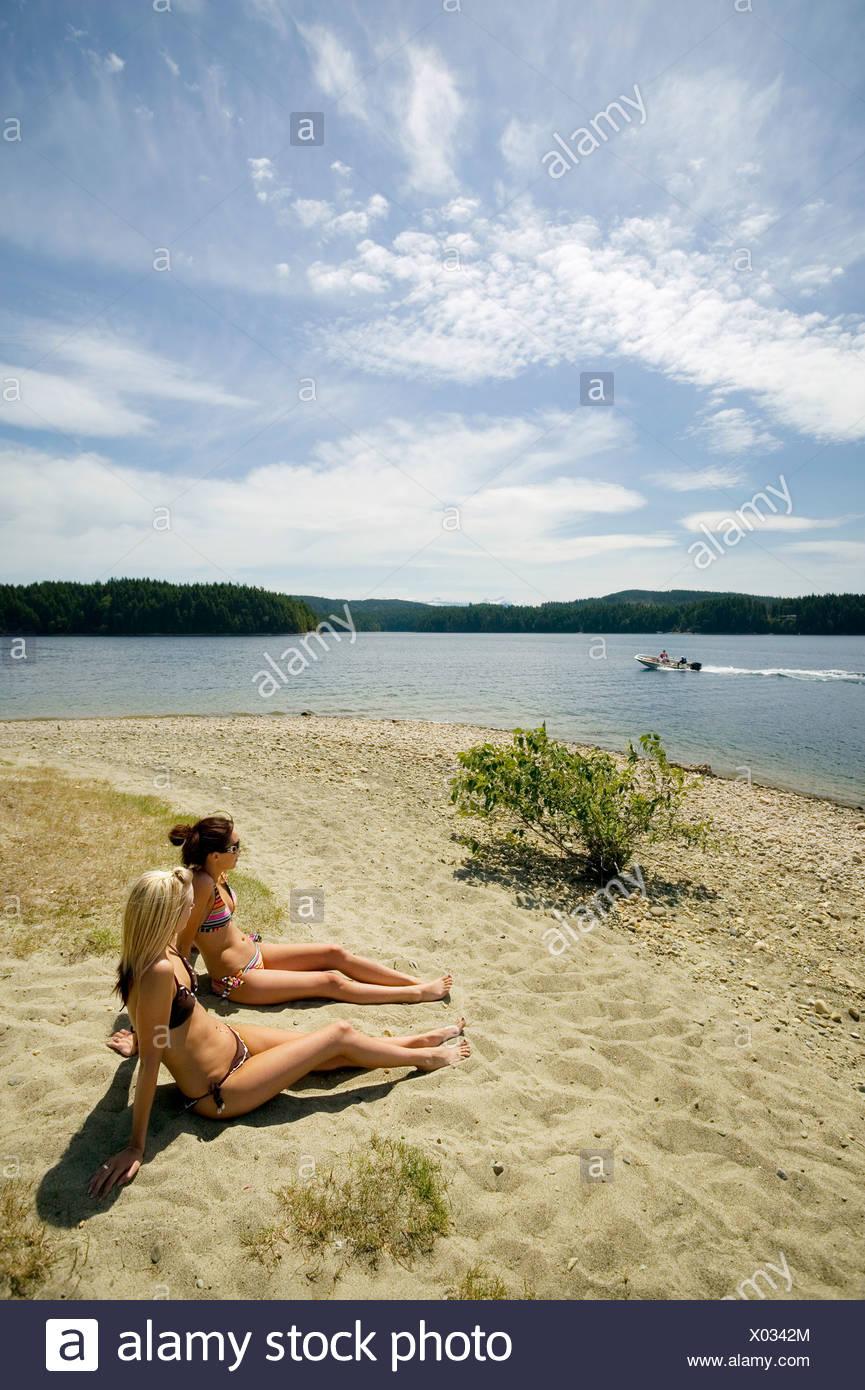 Las mujeres jóvenes en la playa en el lago McIvor. Campbell River, la isla de Vancouver, British Columbia, Canadá Imagen De Stock