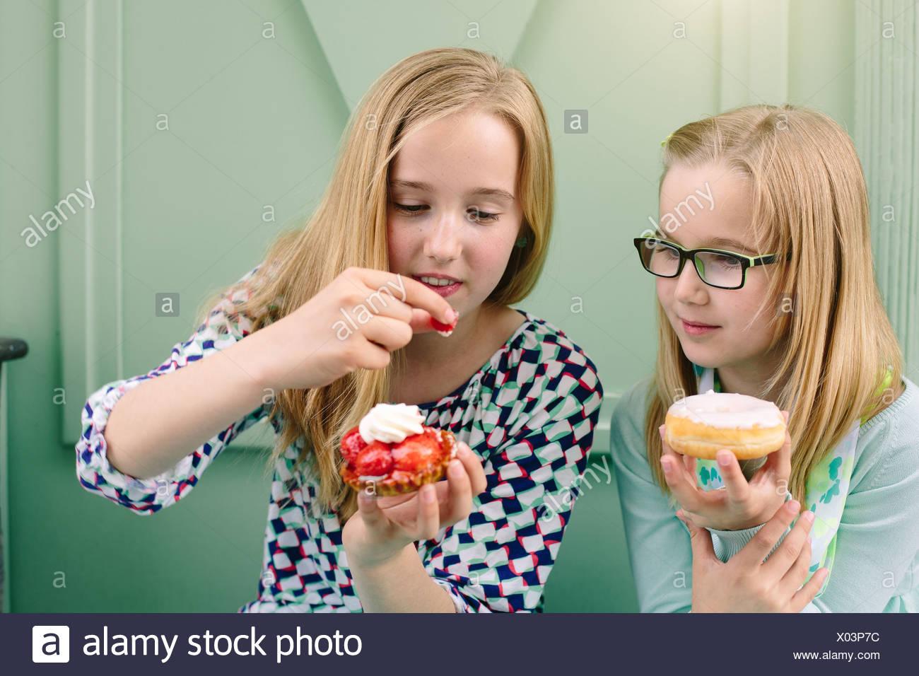Dos hermanas la celebración de pasteles y fresas Imagen De Stock