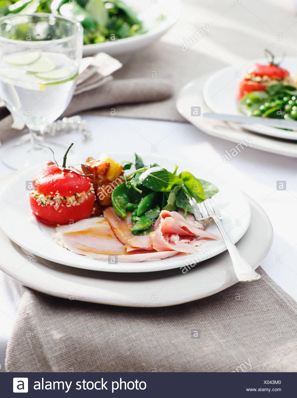 Placas de glaseado jamón con tomates rellenos y espinacas. Imagen De Stock