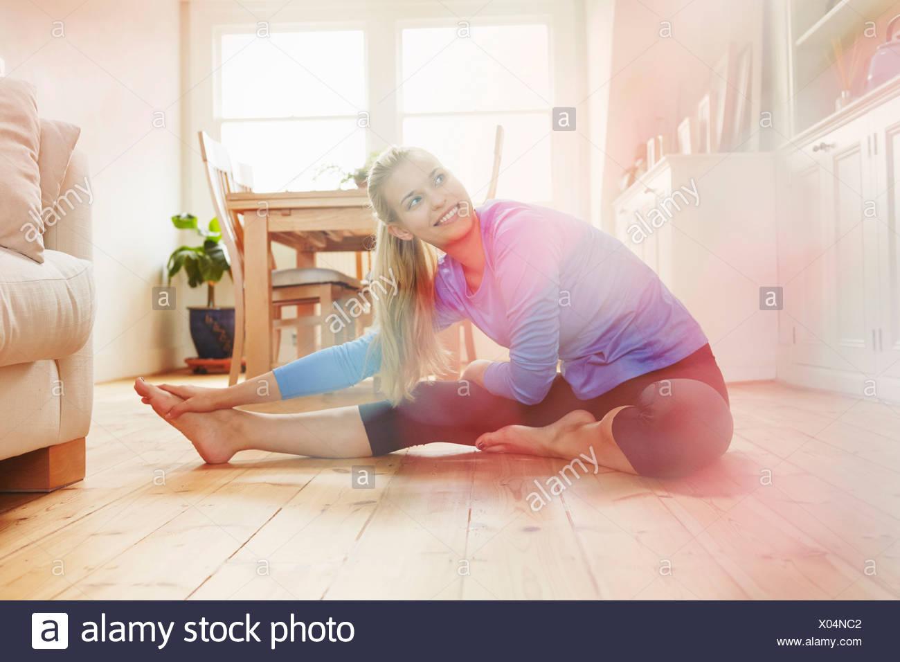 Mujer joven sentada en el suelo vistiendo ropa deportiva, estiramiento Imagen De Stock