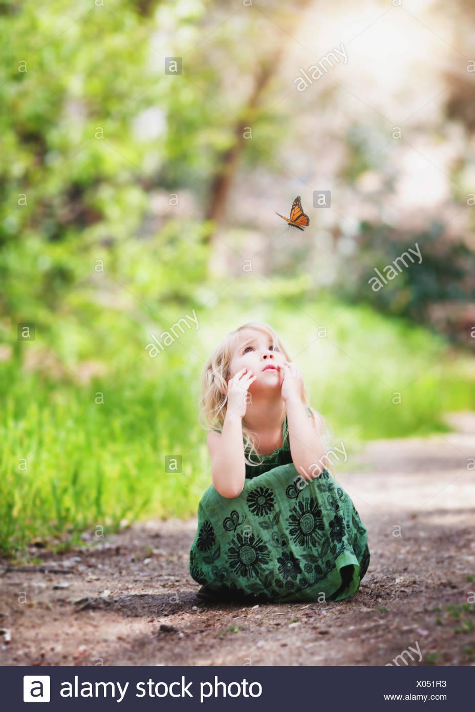 Niña sentada en un camino mirando a una mariposa, California, EE.UU Foto de stock