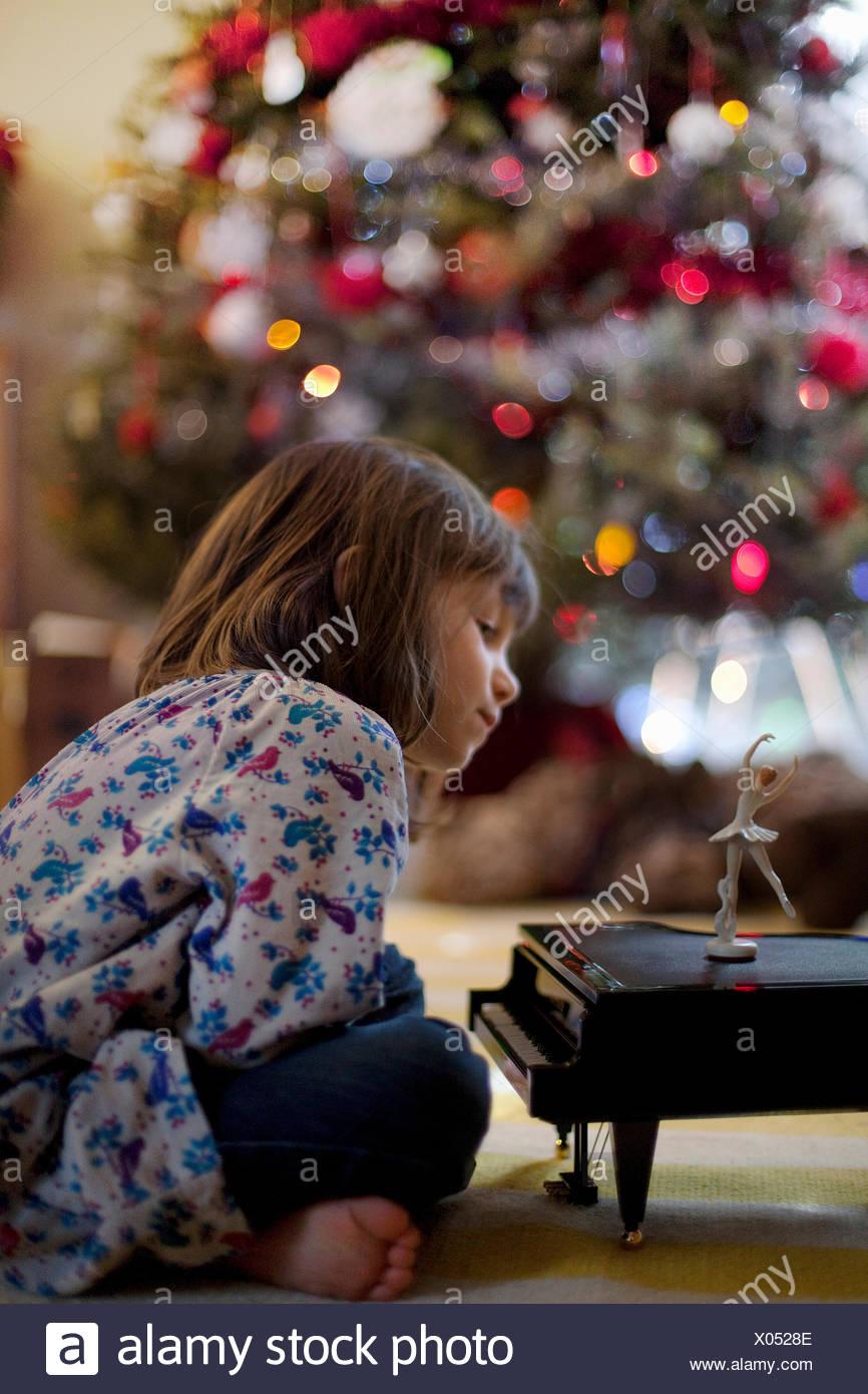 Chica sentada en el suelo del cuarto de estar escuchando música de piano de juguete en Navidad caja Foto de stock
