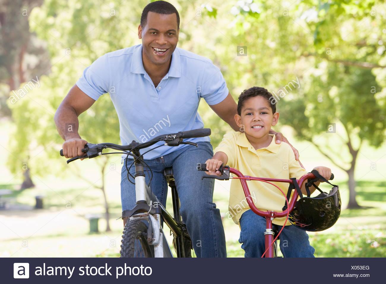 Hombre y muchacho sobre bicicletas afuera sonriendo Foto de stock
