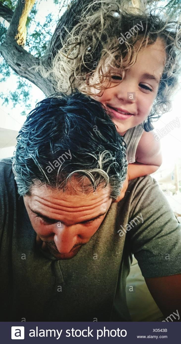 Hijo de padre llevar sobre los hombros contra árboles Imagen De Stock