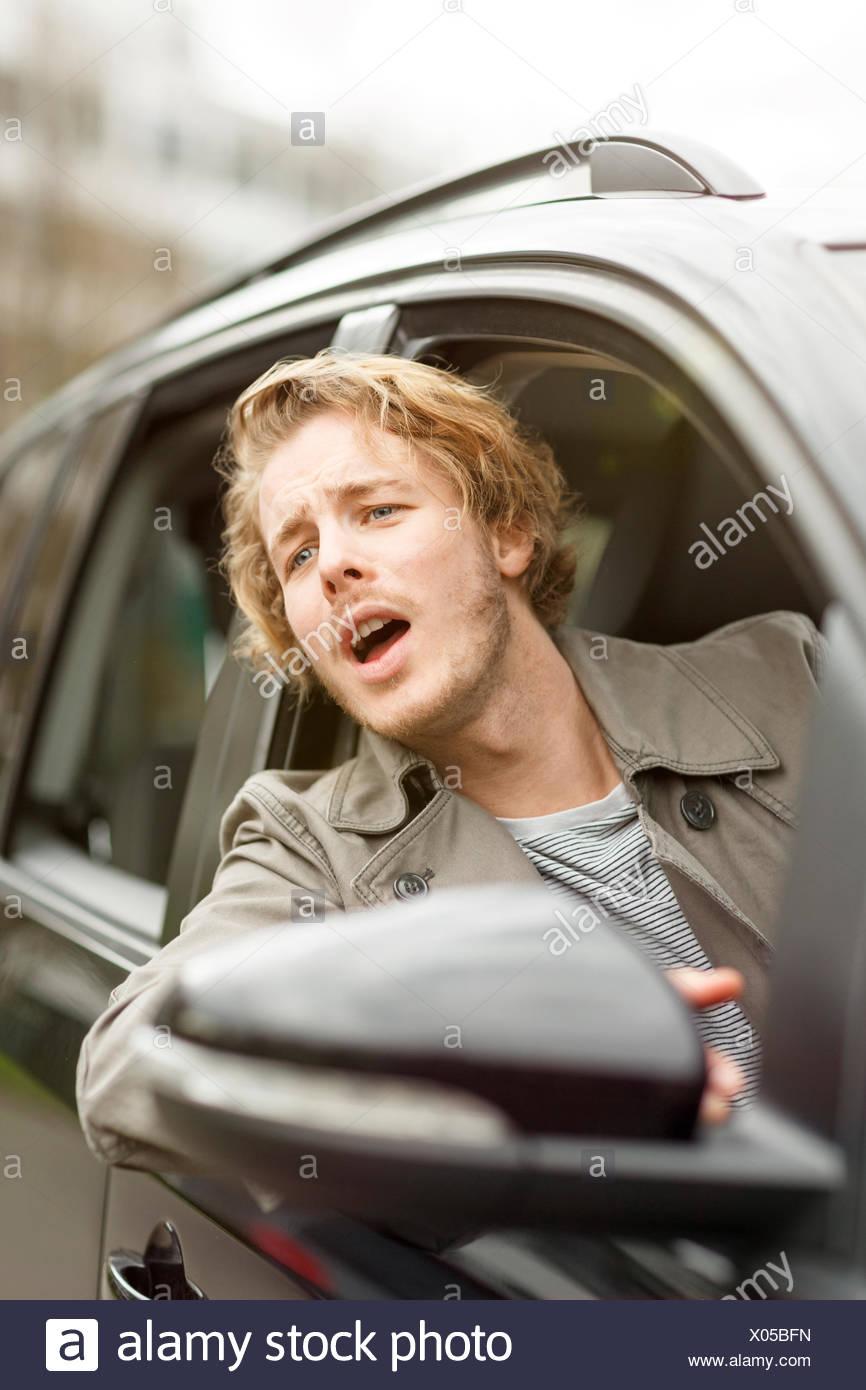 Retrato del joven gritos de asomarse a la ventana de coche Imagen De Stock