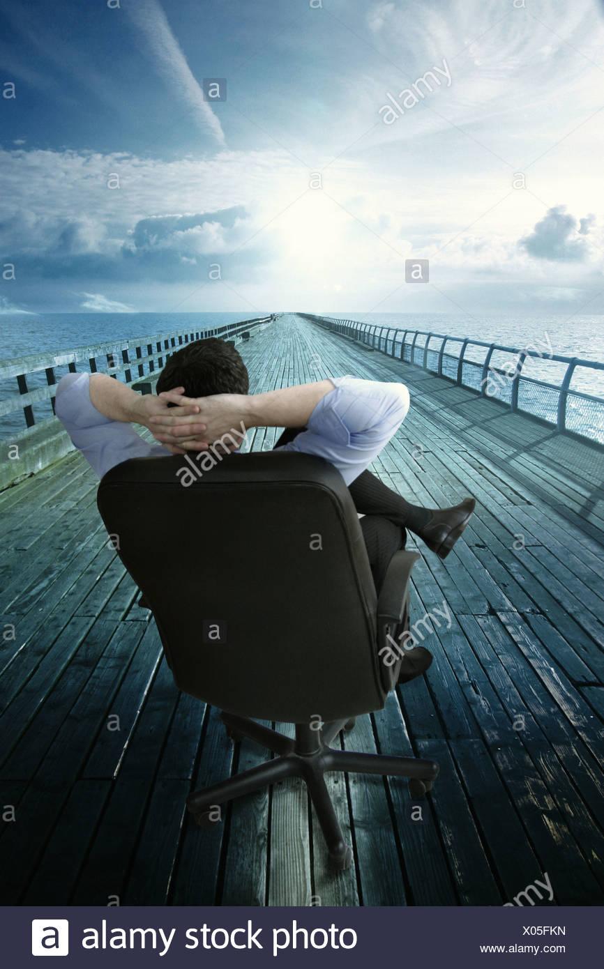 Un hombre de negocios en una silla relajante, mientras que mira el camino Imagen De Stock