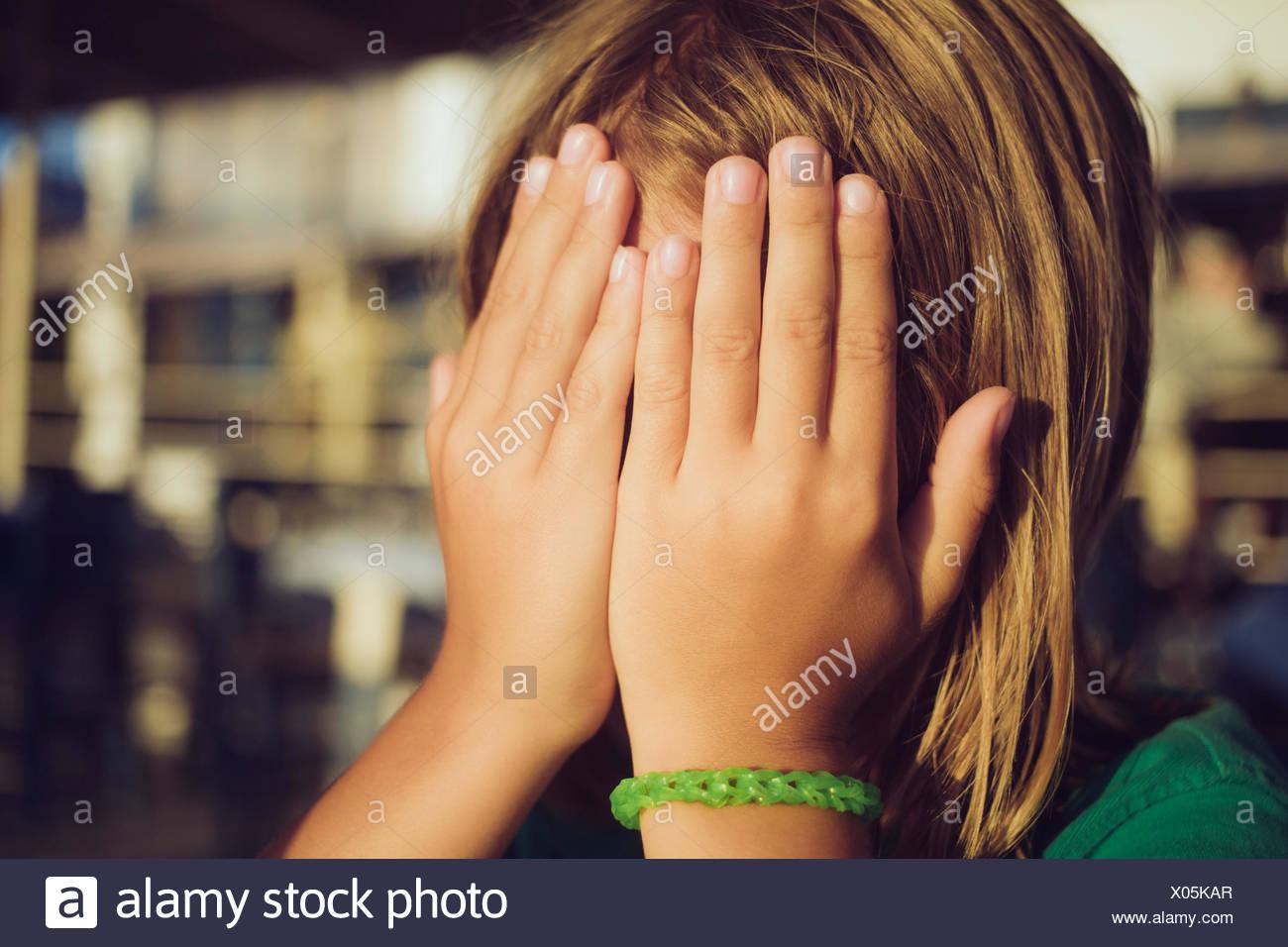 Boy ocultando la cara con las manos Imagen De Stock
