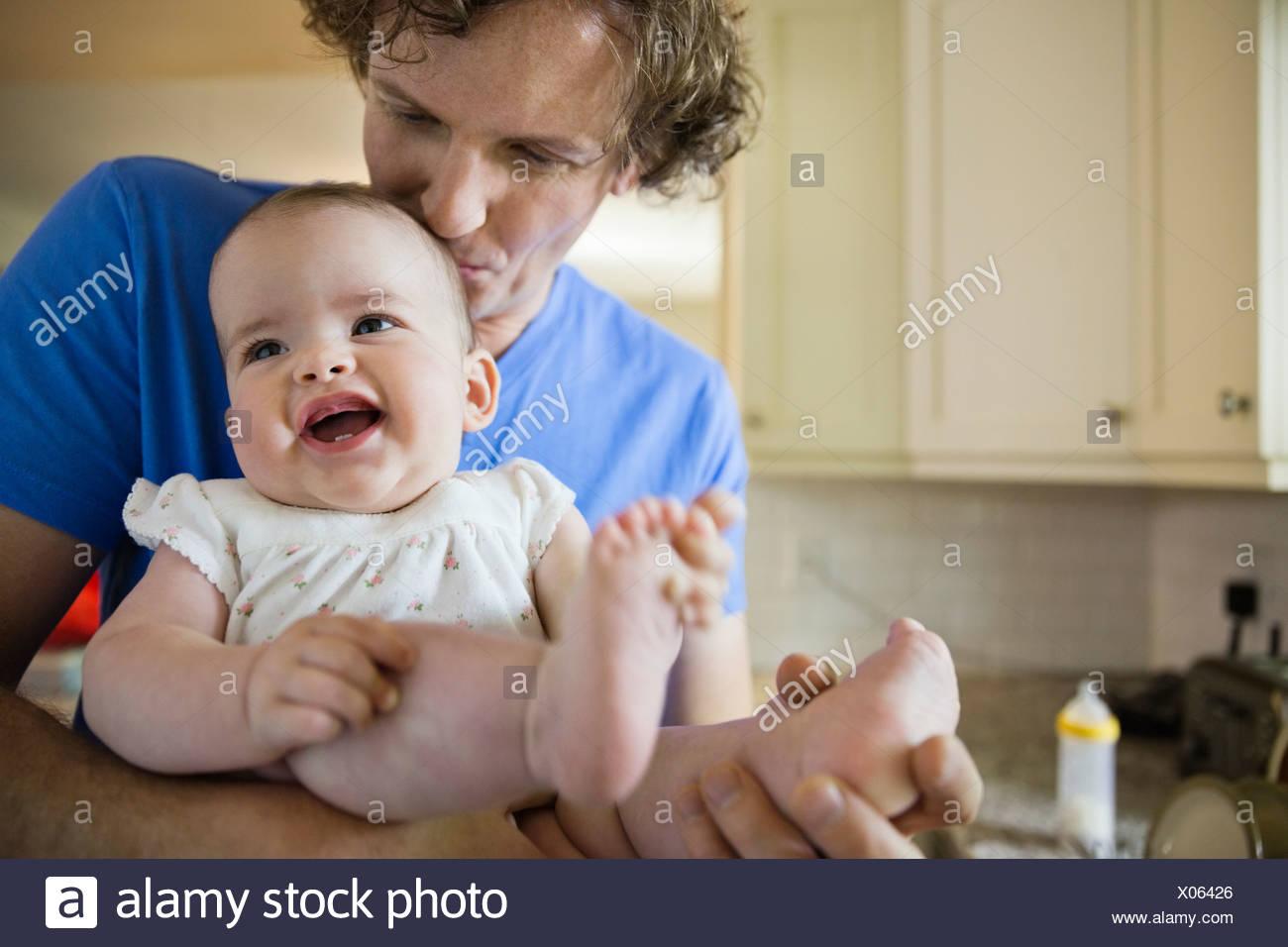 Bebé sonriente celebrada por el p. Imagen De Stock