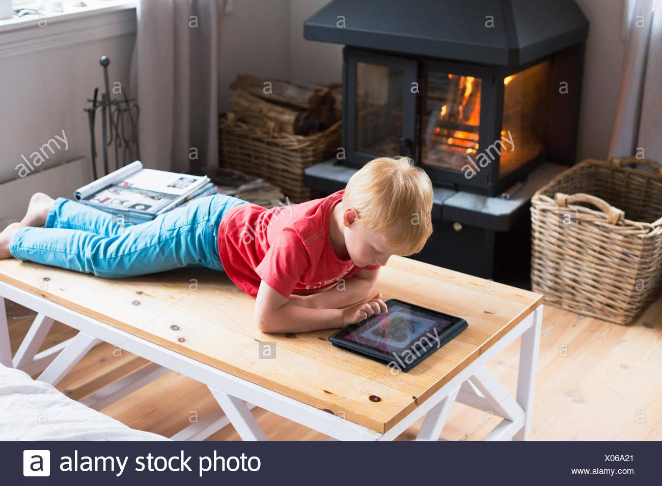 Suecia, archipiélago de Estocolmo, Grasko, Boy (6-7) jugando con la tableta digital en casa Imagen De Stock