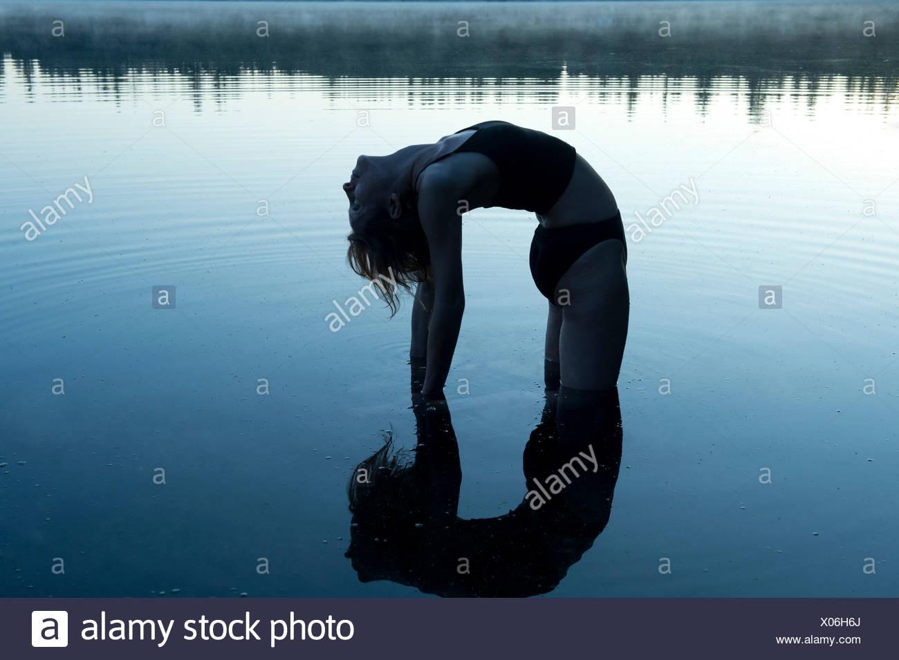 Mujer doblando hacia atrás en el lago Imagen De Stock