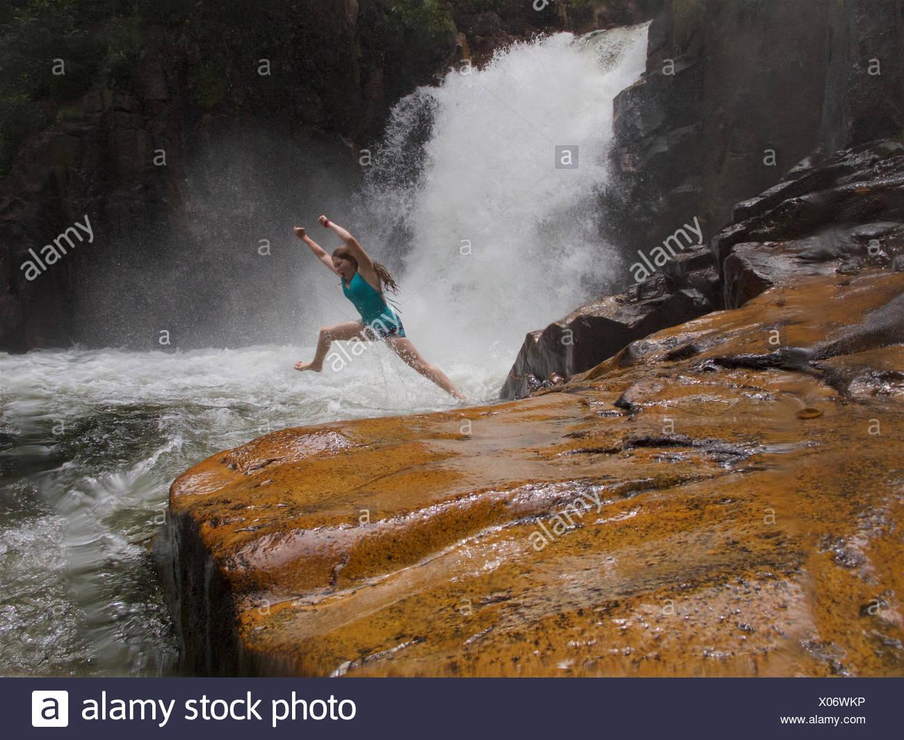Una niña salta en el agua debajo de Riam Berasap, las caídas de las nieblas, que es la cascada más grande en el Parque Nacional Gunung Palung. Imagen De Stock