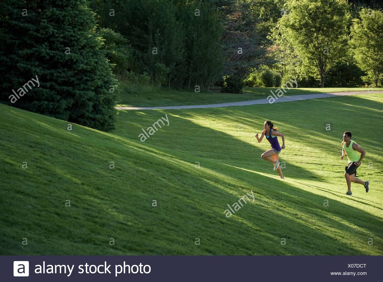 Joven Hombre y mujer haciendo entrenamientos en la colina en el parque Imagen De Stock