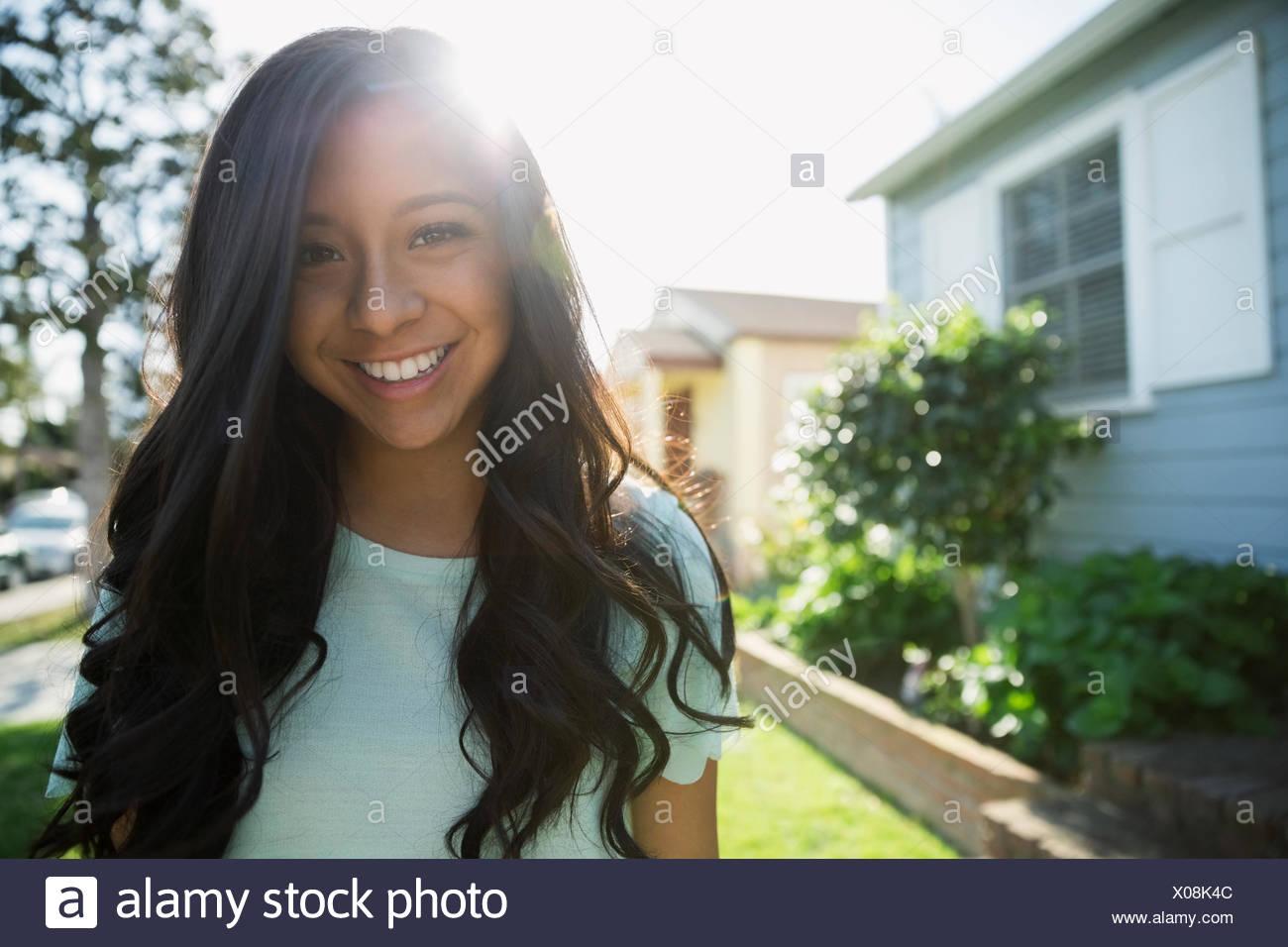 Retrato morena sonriente adolescente soleado patio delantero Foto de stock