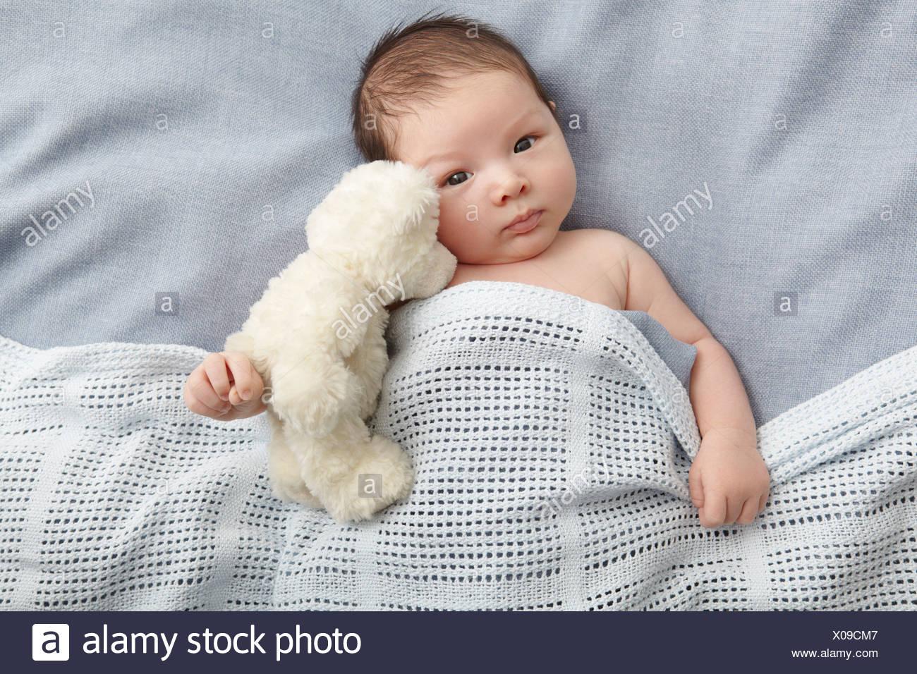 Baby Boy y Teddy bear sentando en la cama Imagen De Stock