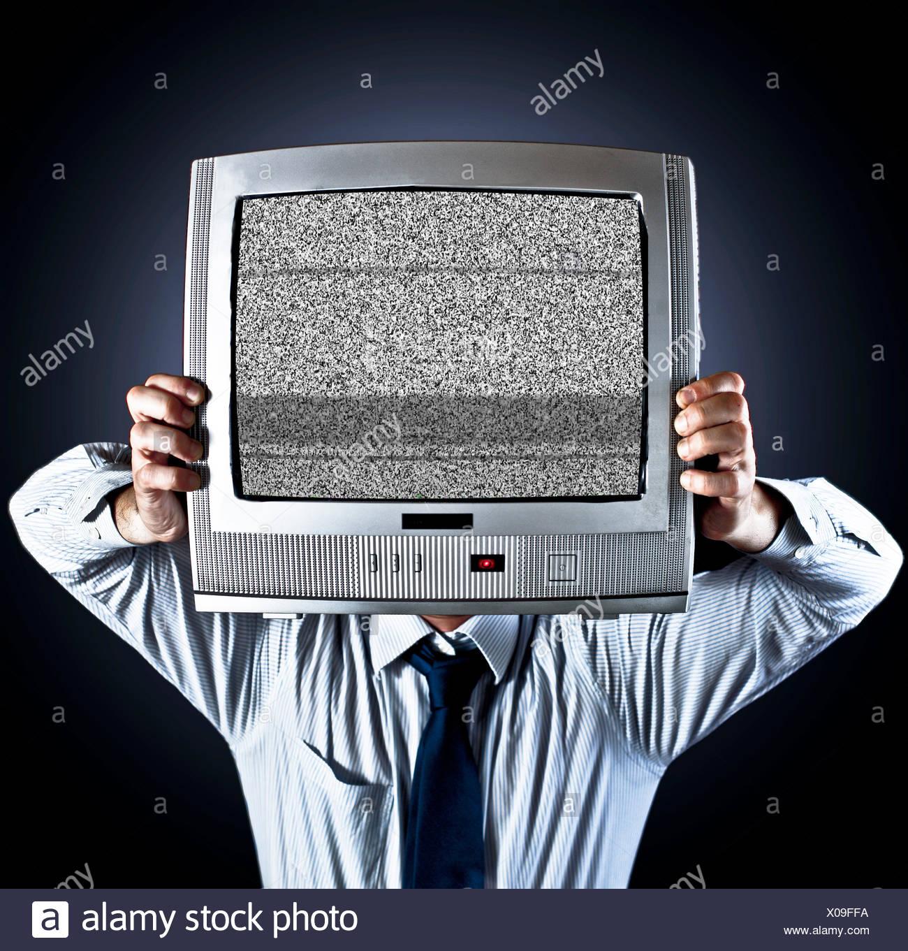 Hombre sujetando la televisión antigua delante de su rostro Imagen De Stock