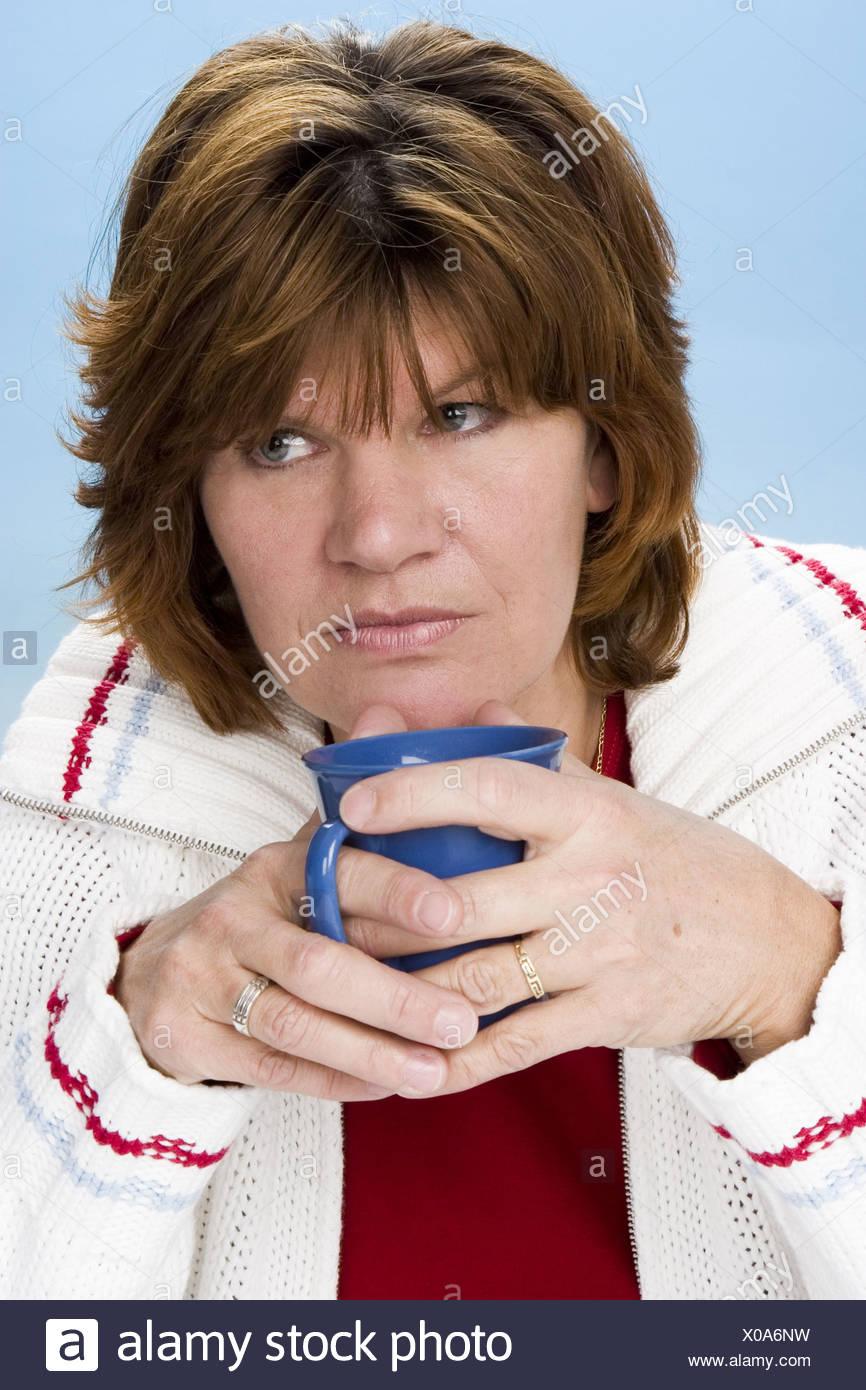 Gruñón mujer blanca adulto bebiendo café y contemplando Foto de stock