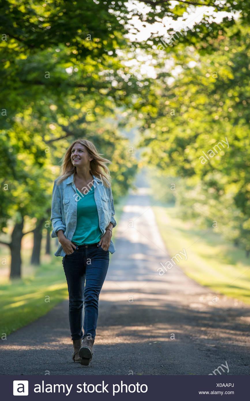 Una mujer caminando por una senda arbolada. Foto de stock