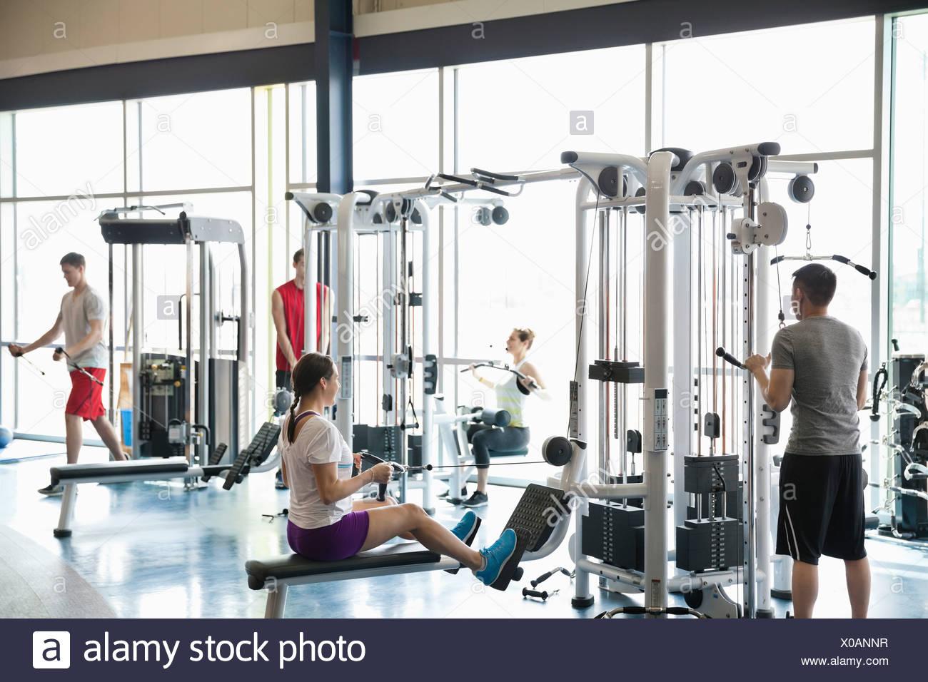 Personas que utilizan máquinas de pesas en el gimnasio Imagen De Stock
