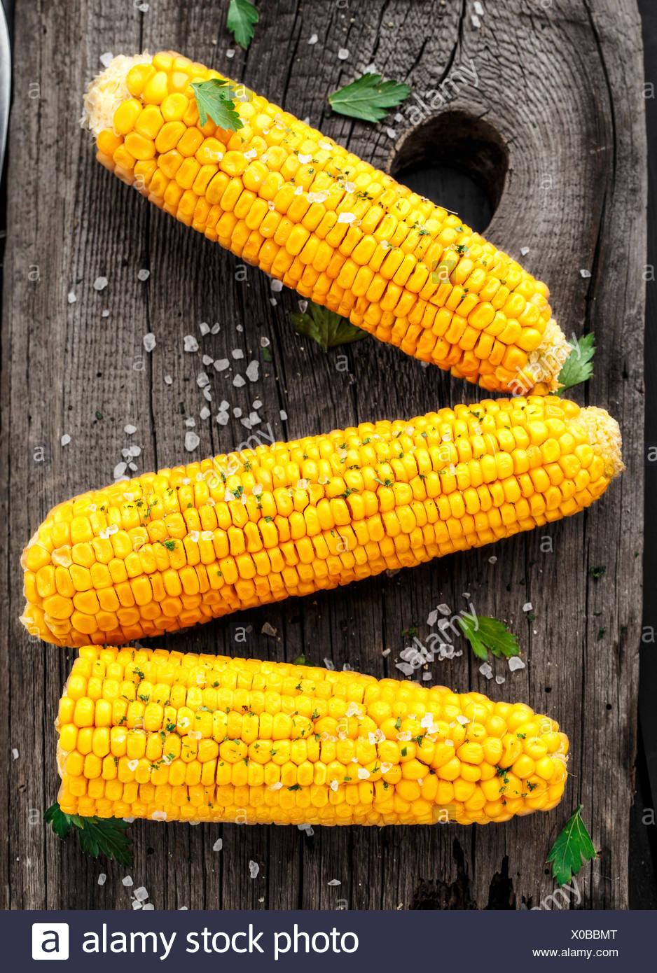 Deliciosas parrilladas de maíz sobre una tabla de madera Imagen De Stock