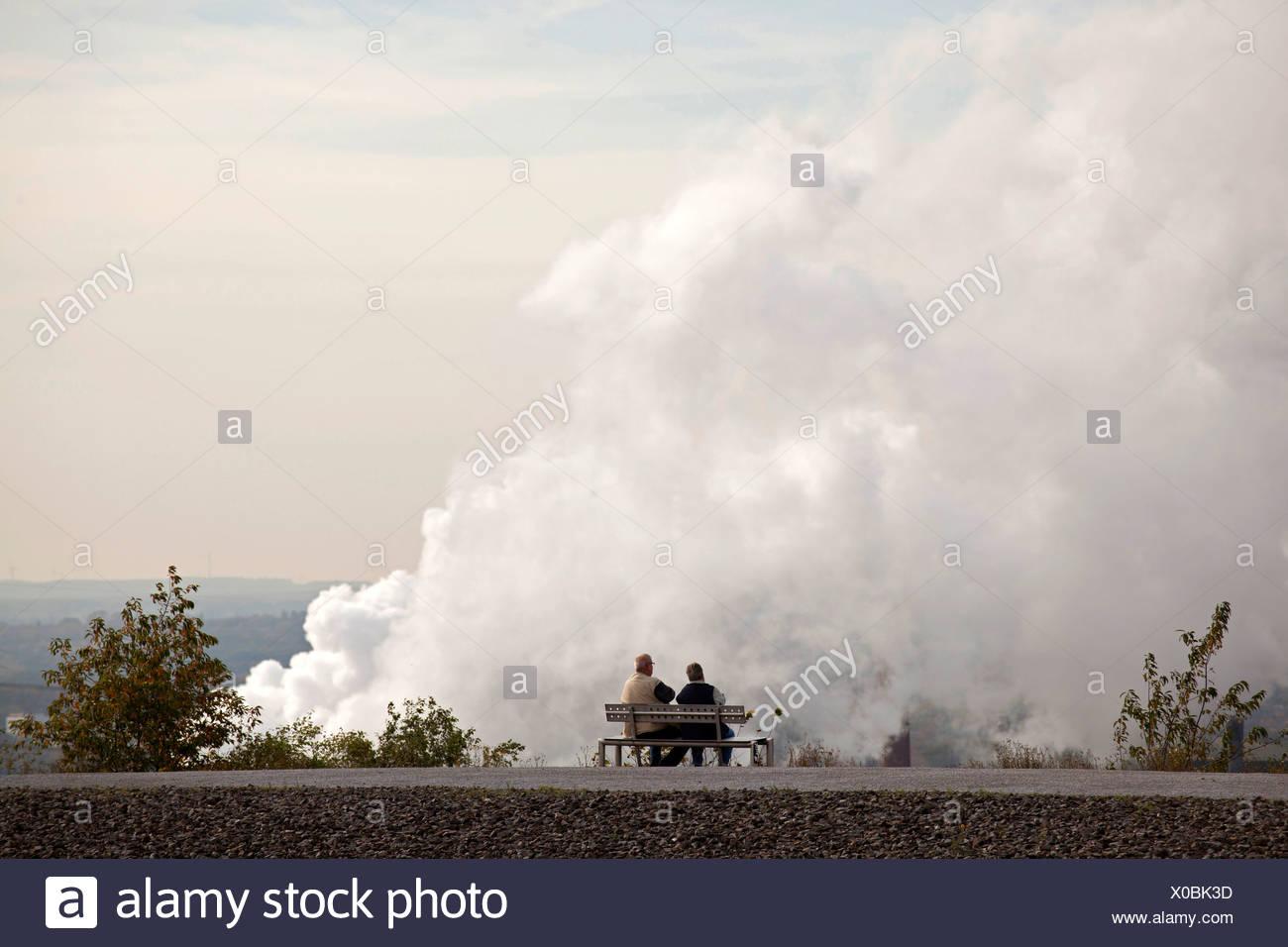 Par en un banco delante de la contaminación atmosférica procedente de una planta eléctrica en Bottrop, área de Ruhr, Renania del Norte-Westfalia Imagen De Stock