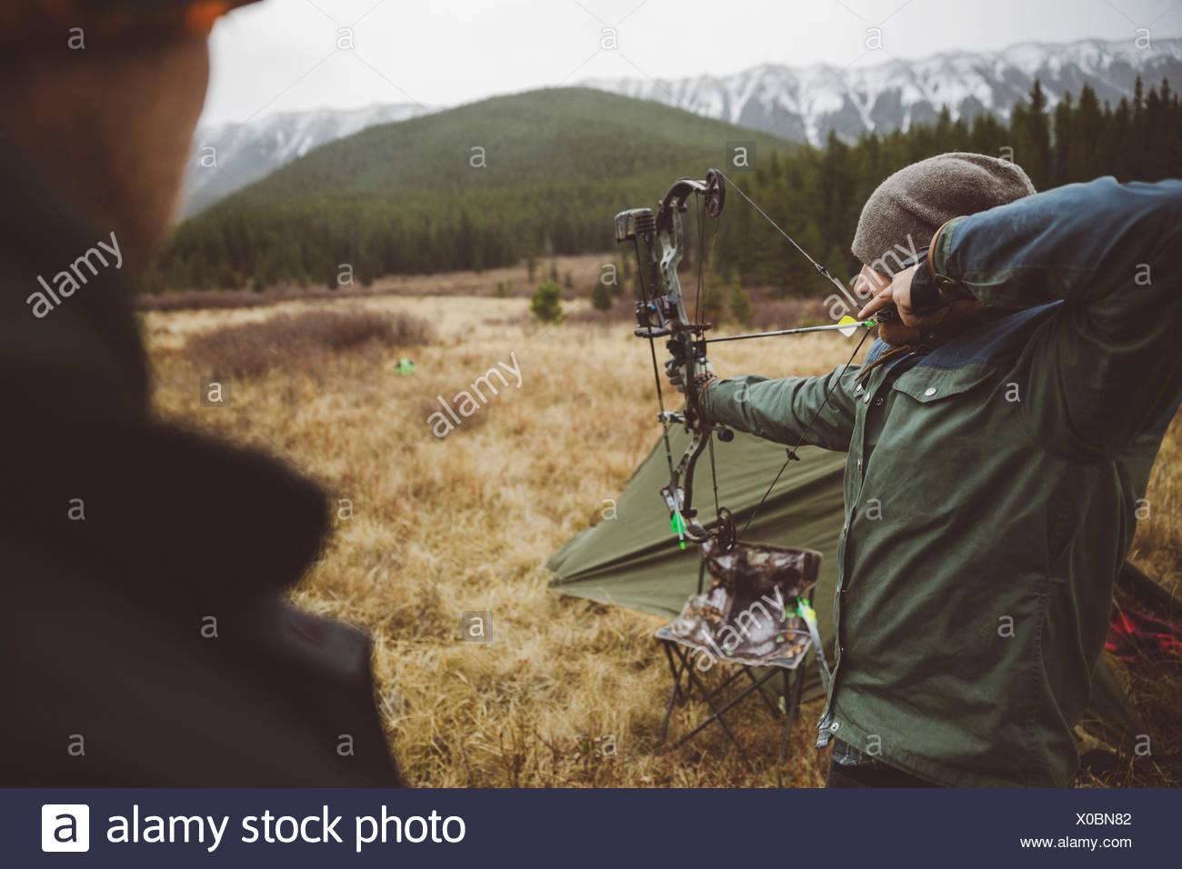 Cazador macho apuntando la caza arco compuesto en campo remoto debajo de las montañas Foto de stock