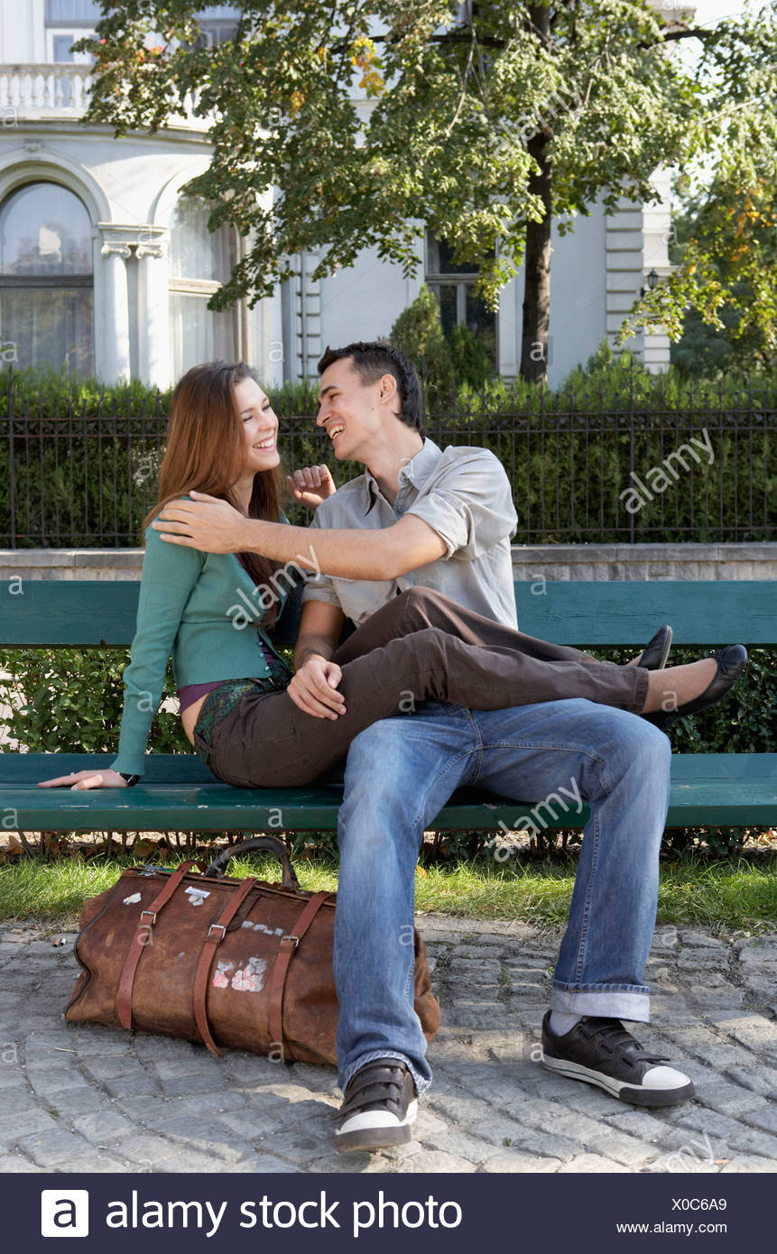 Pareja sentada en un banco riendo. Imagen De Stock