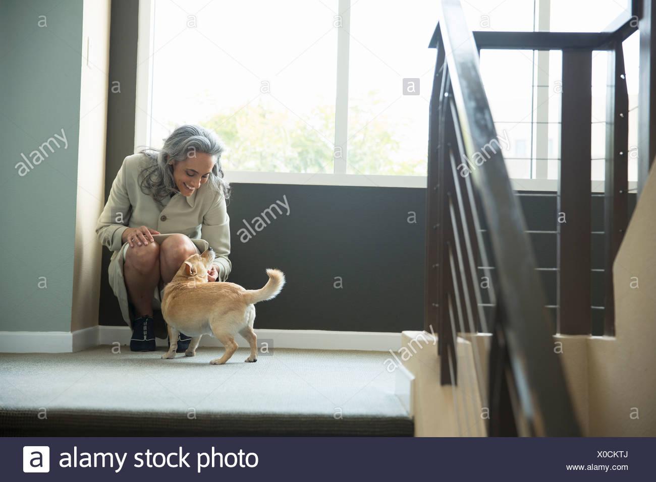 Mujer madura de acariciar a su perro en escalera Imagen De Stock