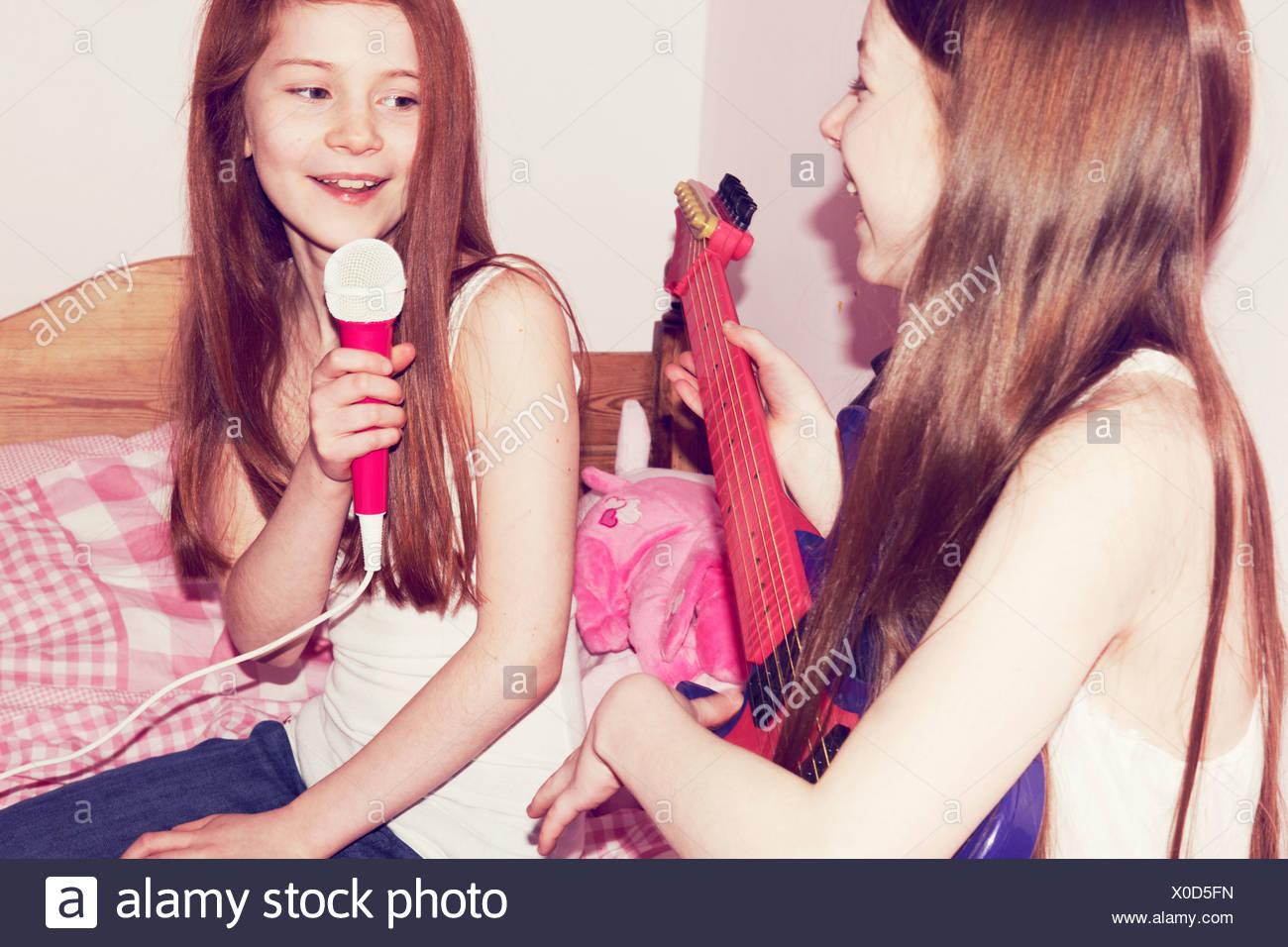Dos niñas tocando la guitarra y cantando en el micrófono en el dormitorio Foto de stock
