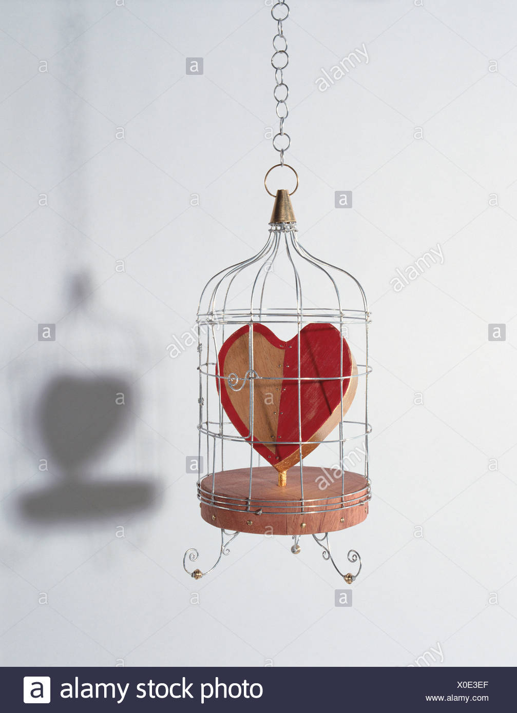 Amor de madera Colgante corazón atrapado en una forma de jaula de metal, corazón pintado mitad rojo, base de madera maciza Foto de stock