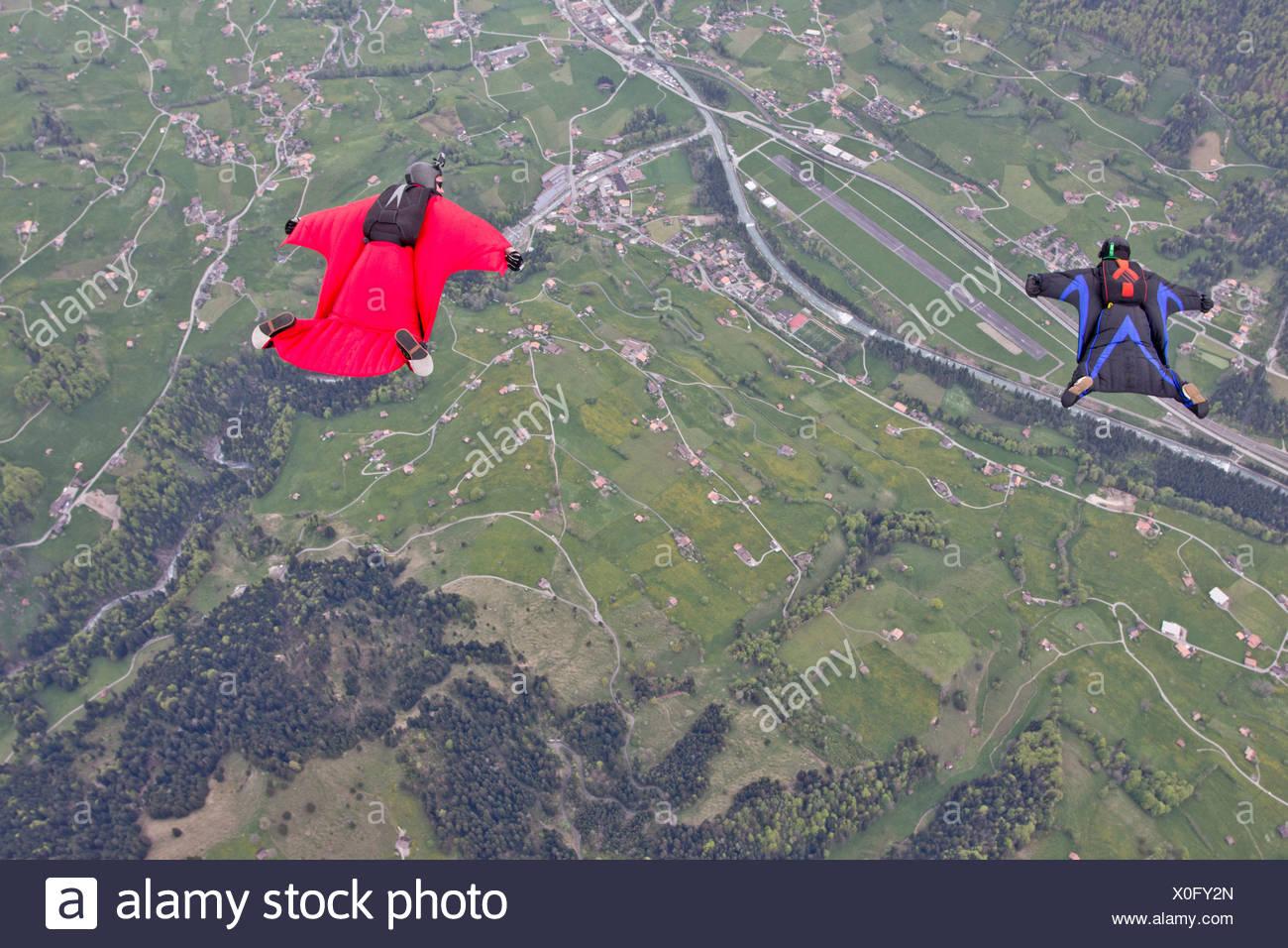 Dos hombres volando por encima de campos en wingsuits Imagen De Stock