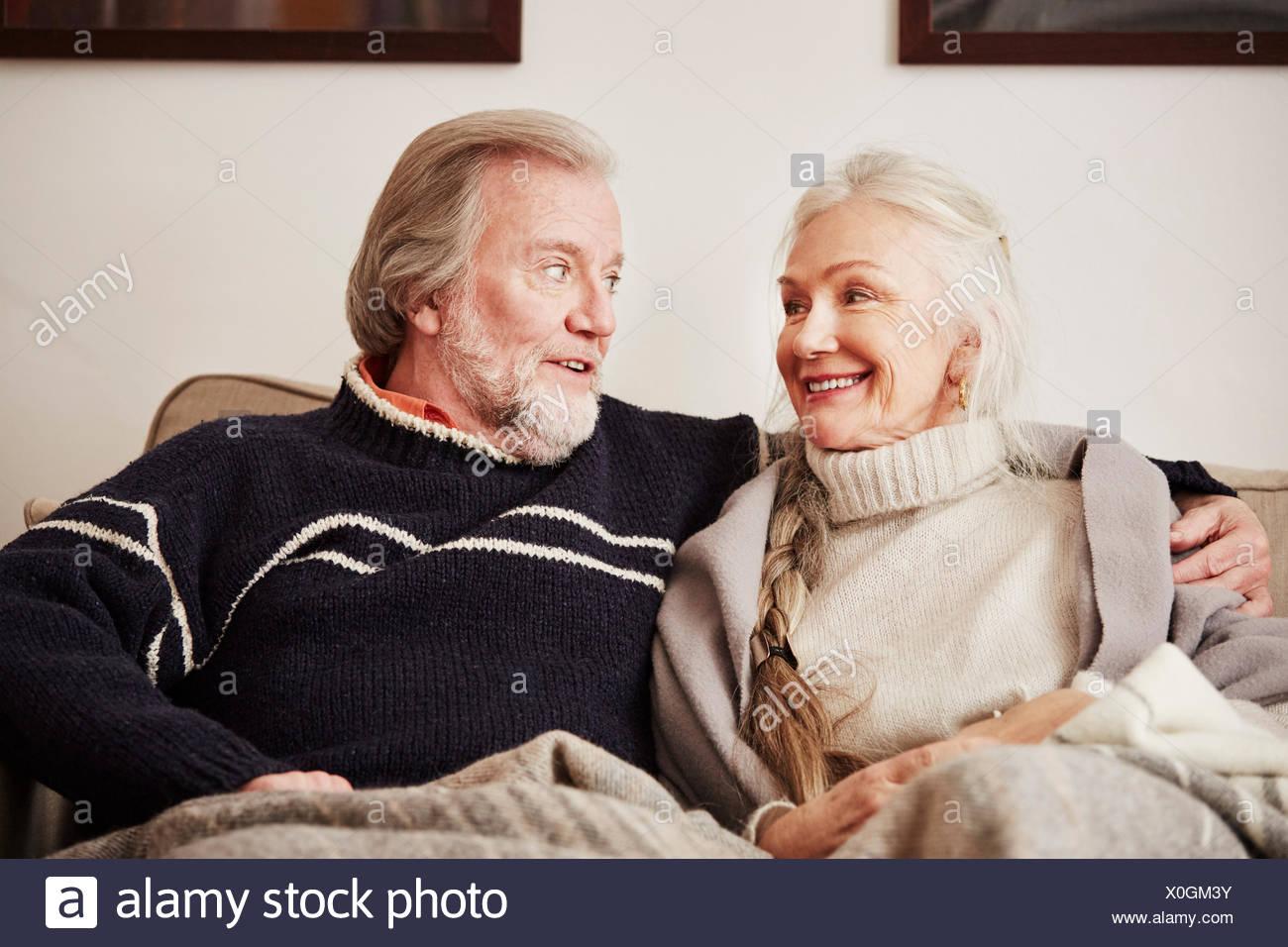 Senior pareja sentada en un sofá, sonriendo Foto de stock