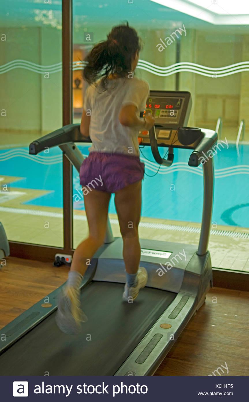Joven en un gimnasio riendo mientras que correr sobre una cinta sin fin Foto de stock