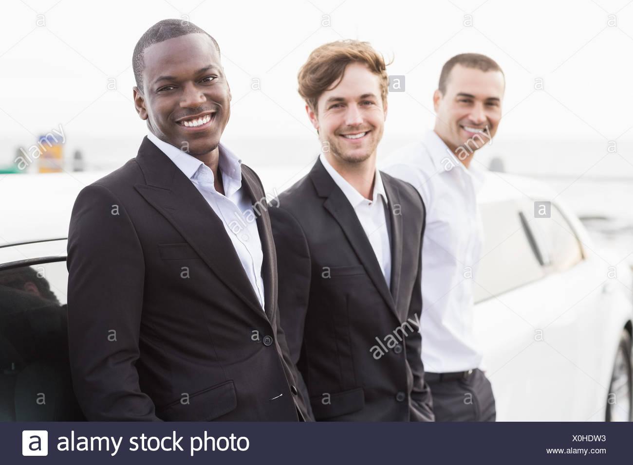 Los Hombres Bien Vestidos Posando Recostado En Una Limusina