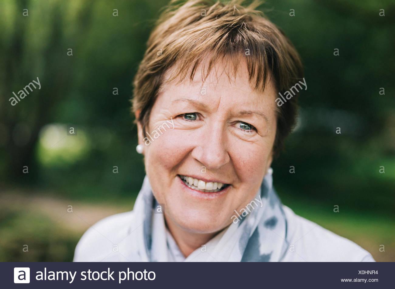 Una mujer madura con corta pelo castaño sonriente. Imagen De Stock