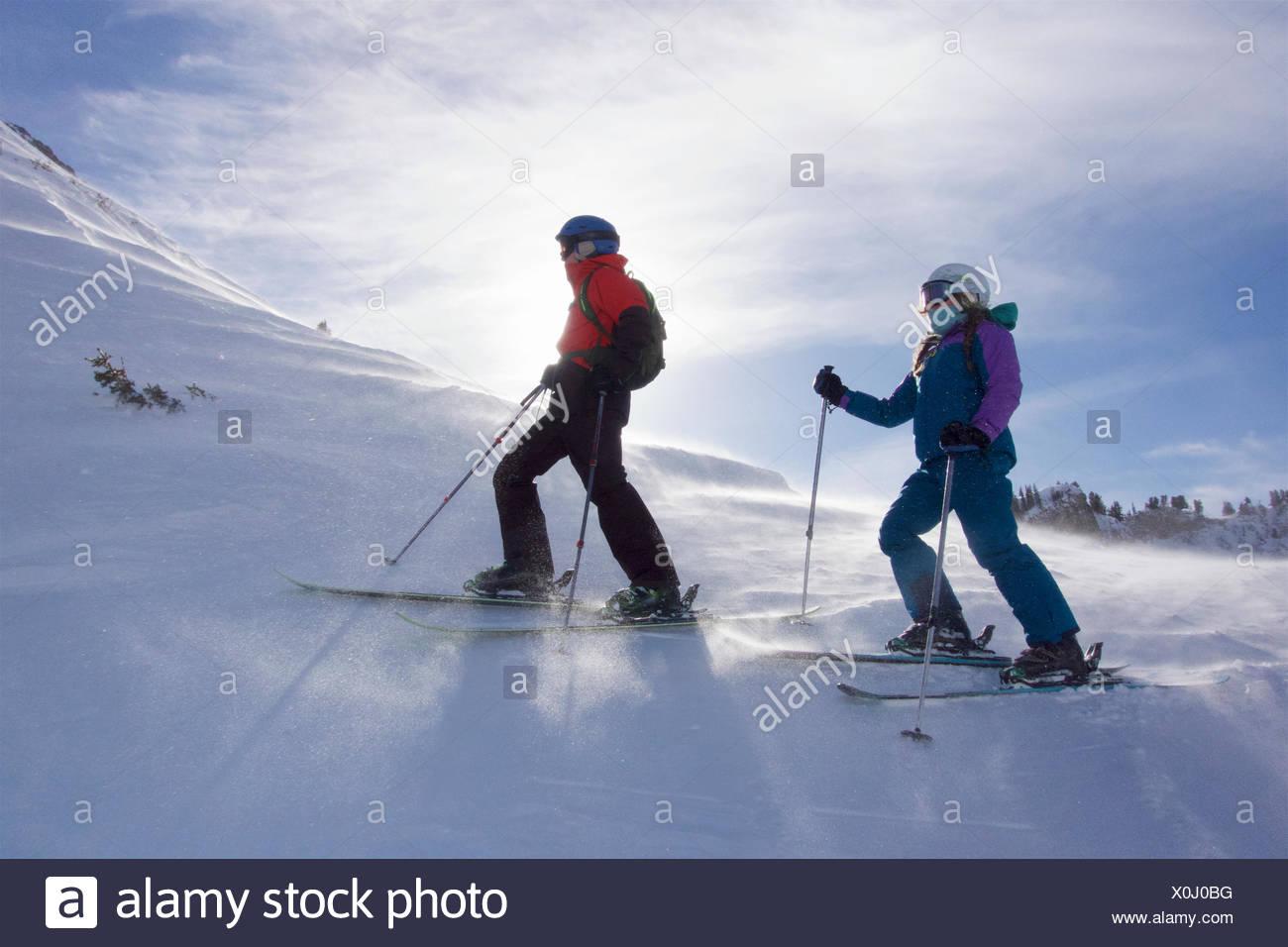 Hermanos adolescentes esquí a través de la cima de una montaña en un día soleado. Imagen De Stock
