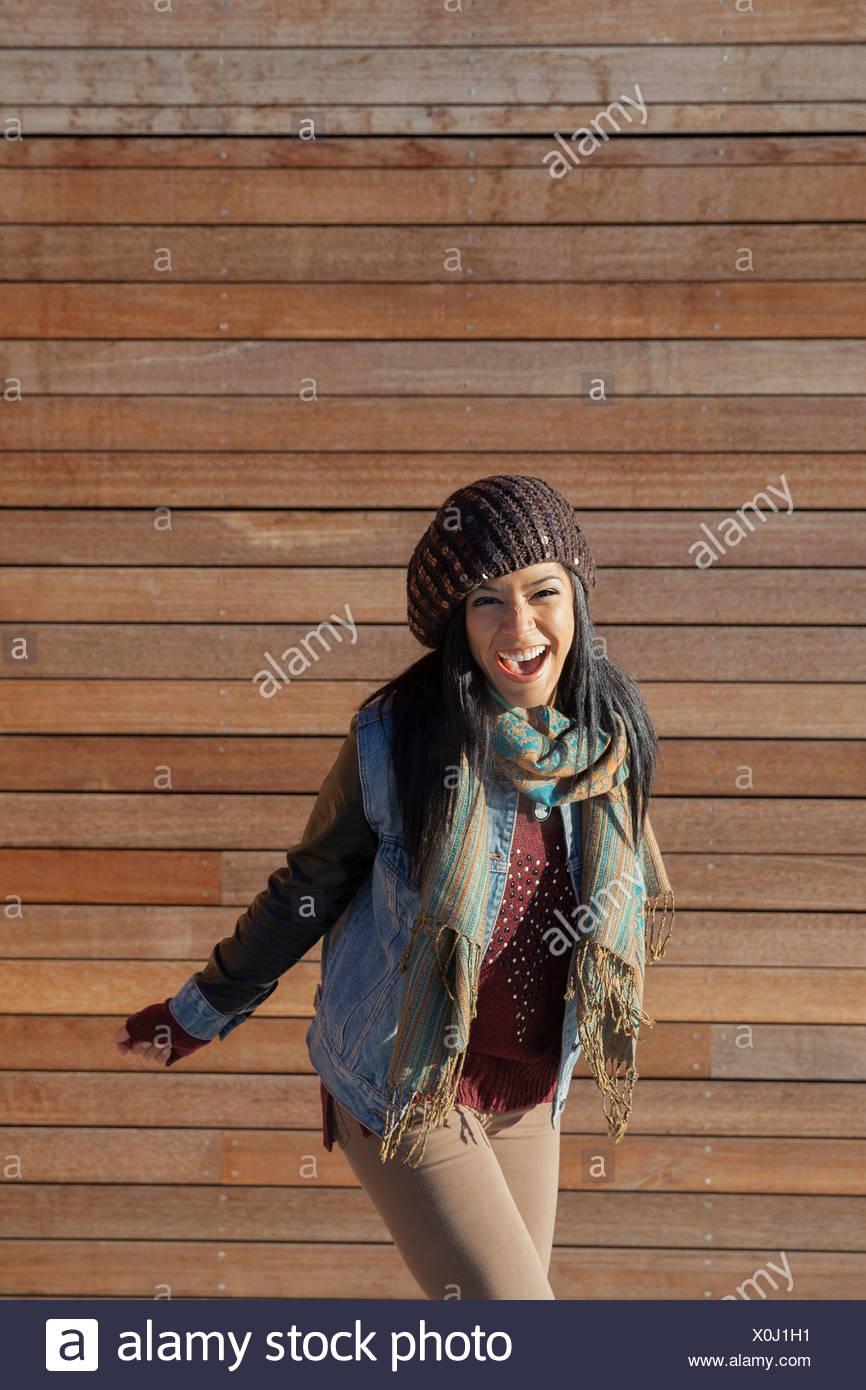 Mujer de pie juguetona en contra de paneles de madera en el exterior Imagen De Stock