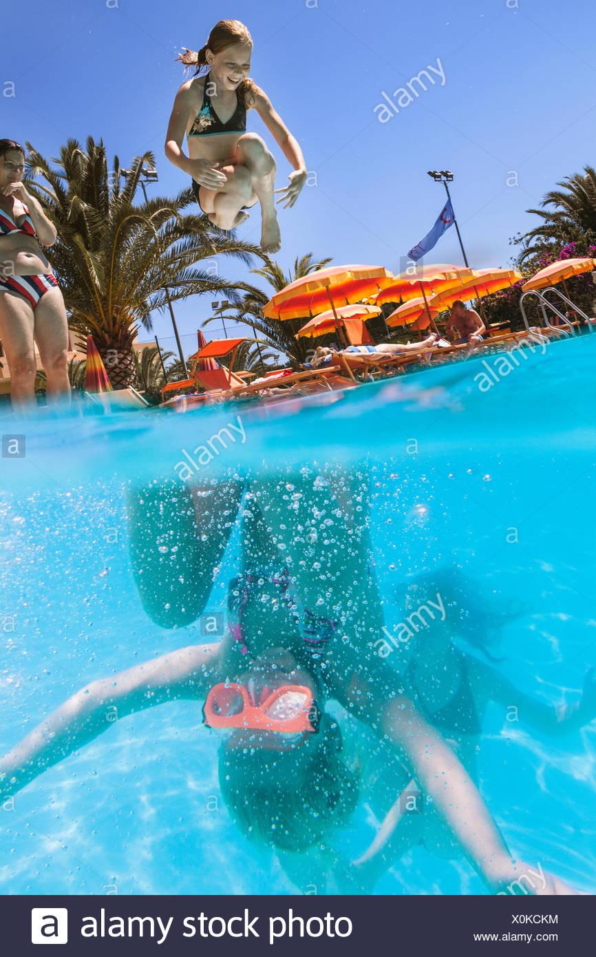 Italia, Cerdeña, Alghero, Madre viendo los niños (14-15, 16-17) buceo en piscina Foto de stock