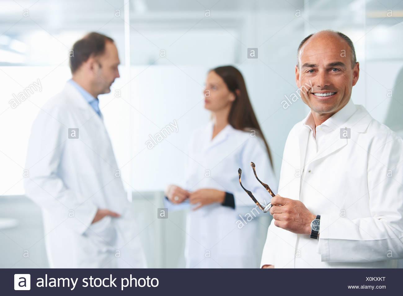 Médico varón por pared reflectante, colegas en segundo plano. Foto de stock