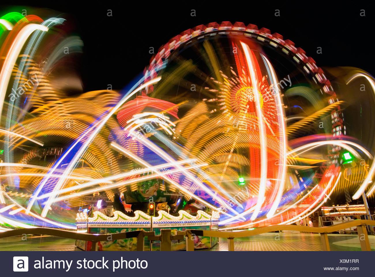 Las luces brillantes de paseos en un parque de diversiones Foto de stock