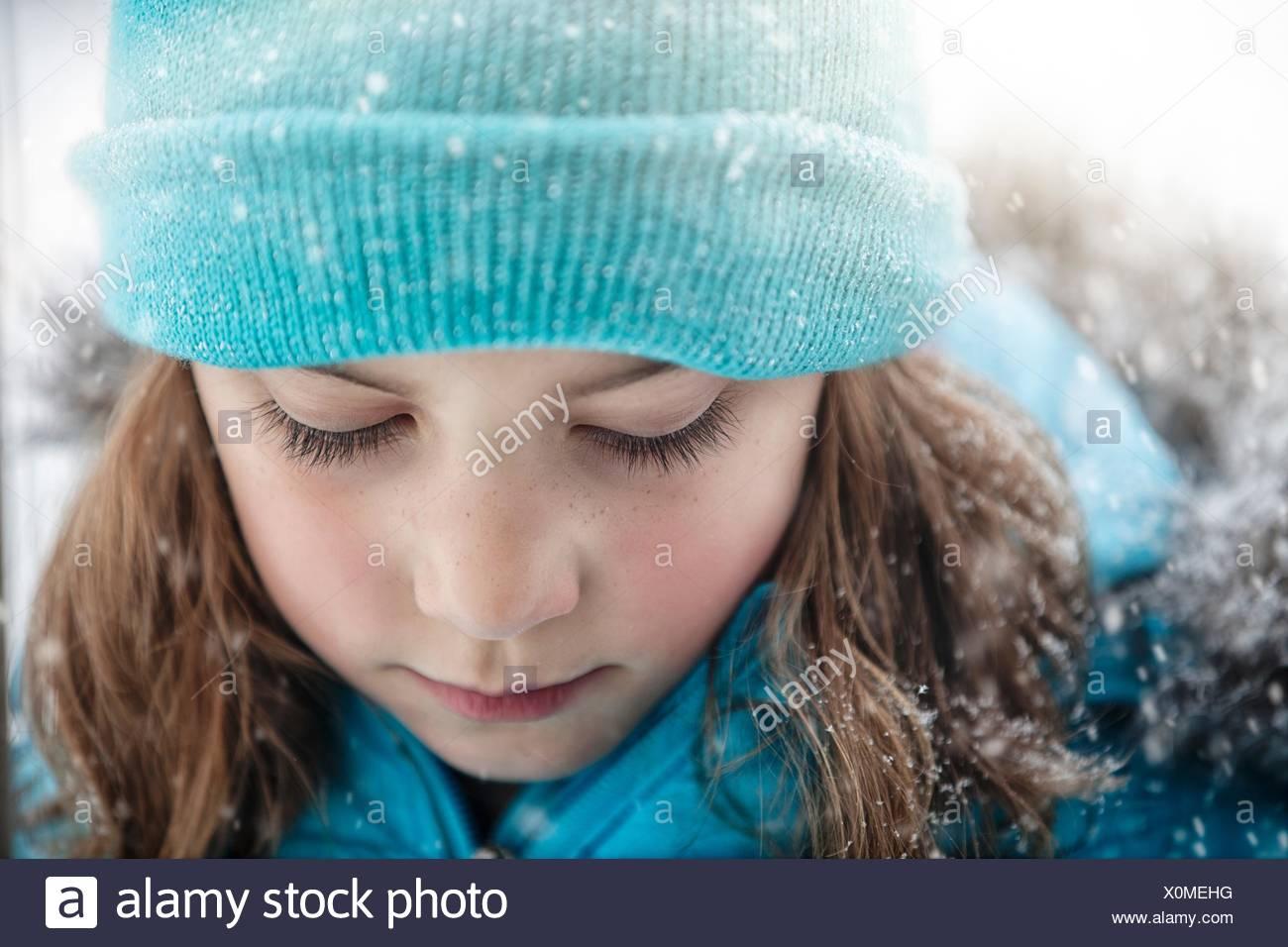 Close Up retrato de chica que llevaba knit hat mirando hacia abajo, nevando Foto de stock
