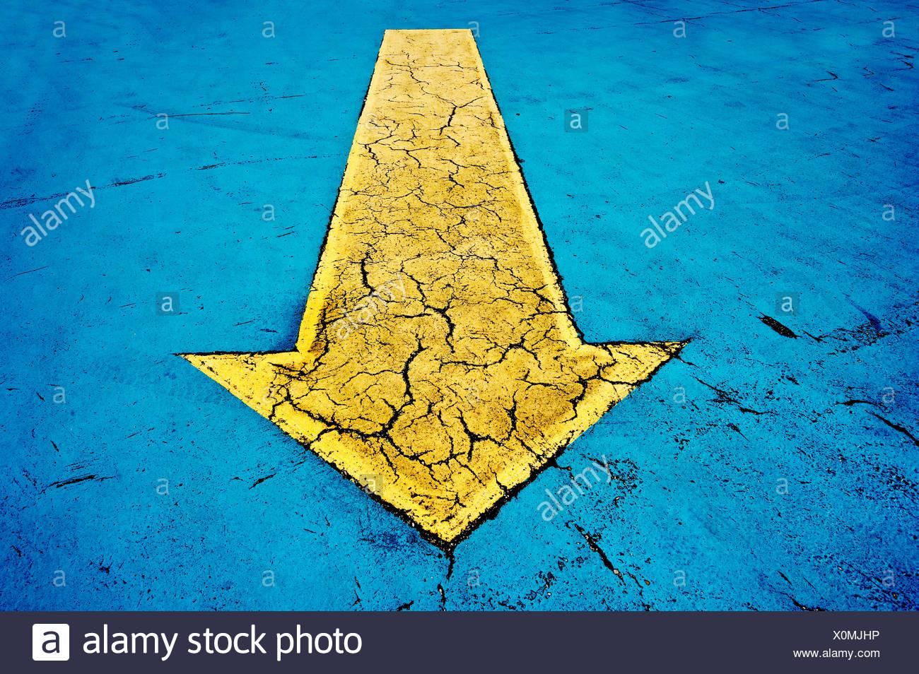 Flecha amarilla en azul con grietas de hormigón Imagen De Stock