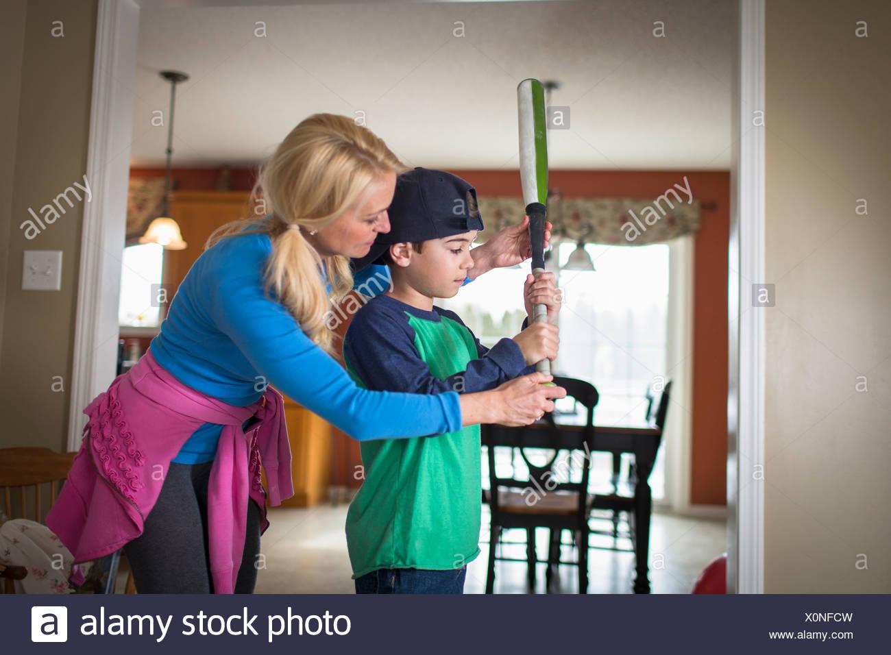 Madre Hijo docente para sostener un bate de béisbol Imagen De Stock