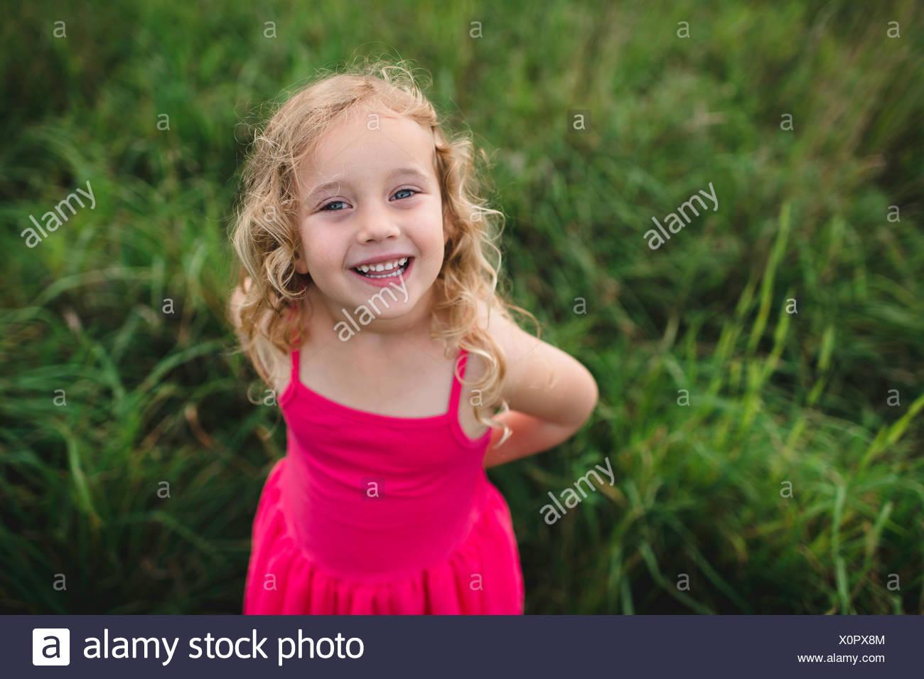 Retrato de la muchacha de los cabellos rubios en hierba Foto de stock