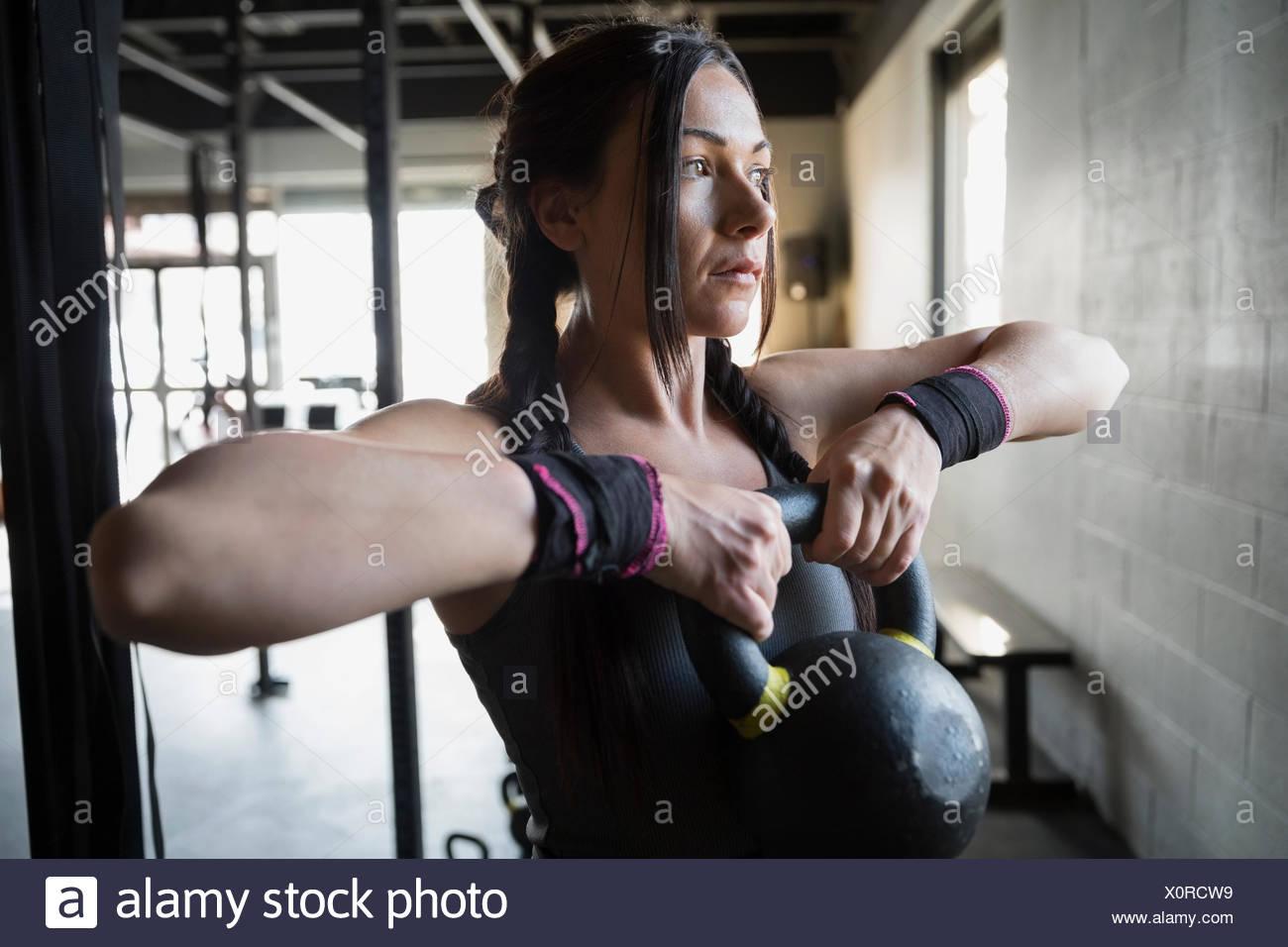 Mujer centrado con kettlebell pesas en el gimnasio Imagen De Stock