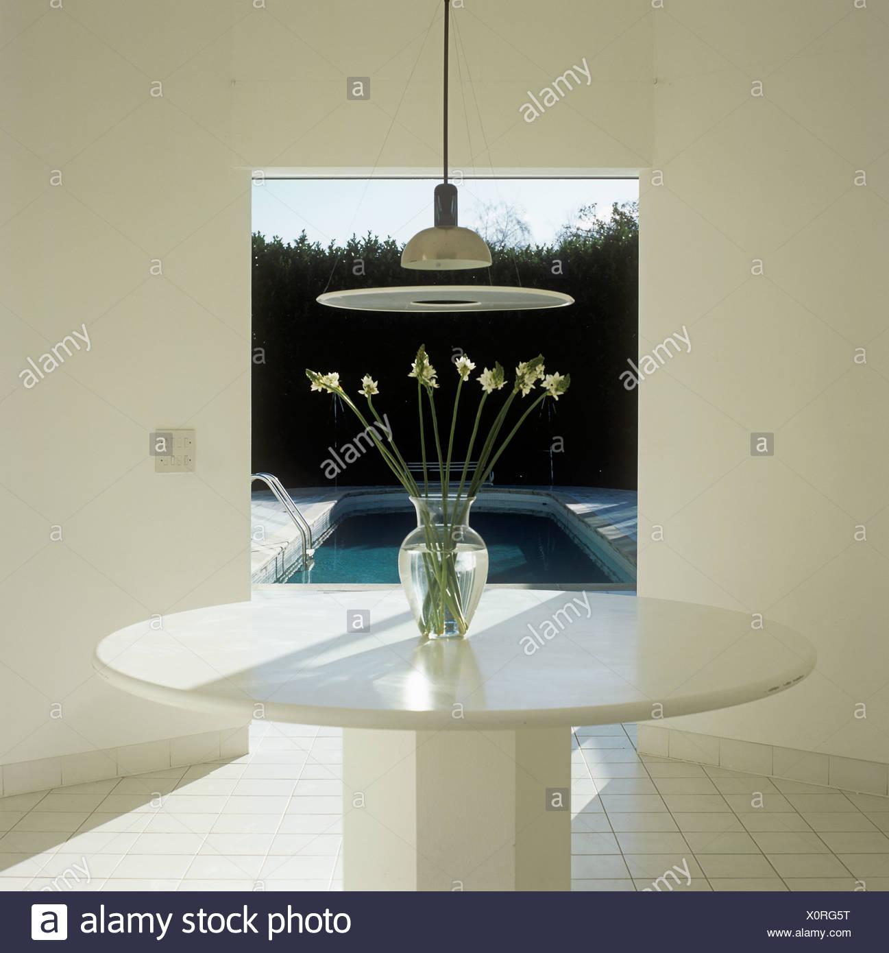 Luz blanca suspendida sobre la mesa en el comedor ...